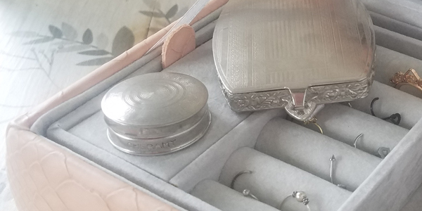 Close up of two silver-toned metal compacts in an open jewelry box. The focus is on a smaller, round rouge pot with simple circular etching on the lid.