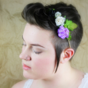 Picture of a person in profile. They have dark hair, light skin, and are wearing paper flowers in their hair.